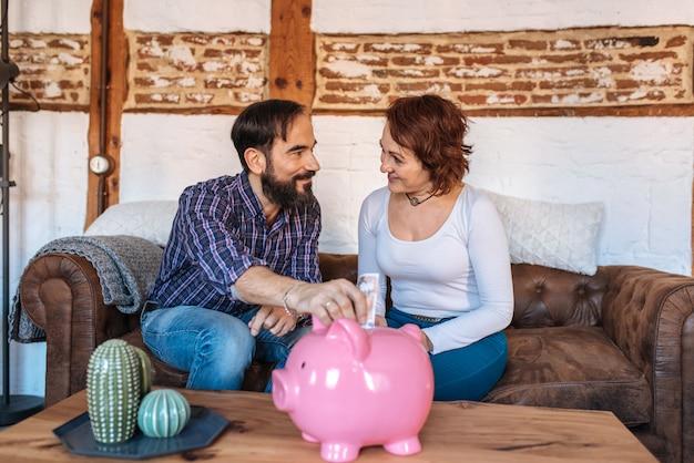 Dorośleć pary relaksował w domu w kanapie oszczędza pieniądze na prosiątko banku