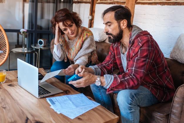 Dorośleć pary siedzi w domu patrzejący ich finansowych problemy