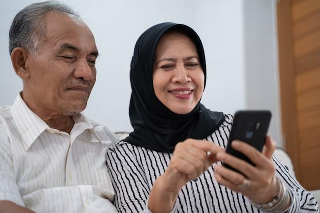 Dorośleć pary używa telefon komórkowego