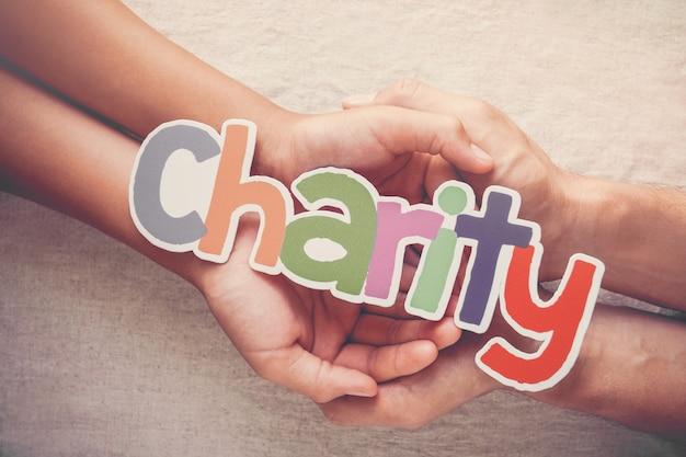 Dorosłego i dziecka ręki trzyma słowa dobroczynności, darowizny i dobroczynności pojęcie