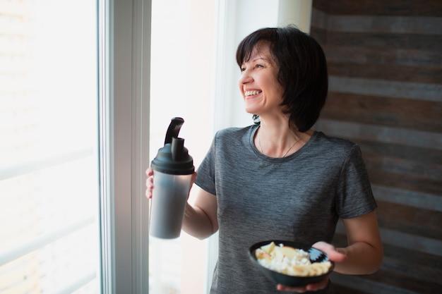 Dorosłego napadu szczupła kobieta pozuje na kamerze. trzymając miskę i butelkę w ręce. jedzenie posiłku po treningu lub ćwiczeniach. ciesząc się jedzeniem samemu w pokoju.