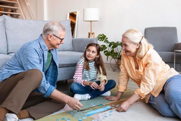 Dorośli i dziewczyna robi puzzle na podłodze