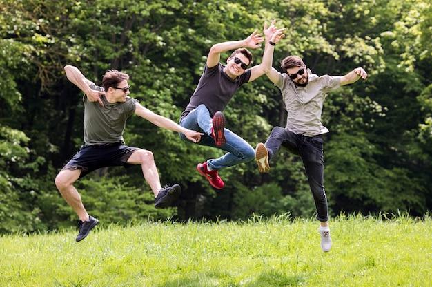 Dorosli mężczyźni pozują i skaczą w powietrzu