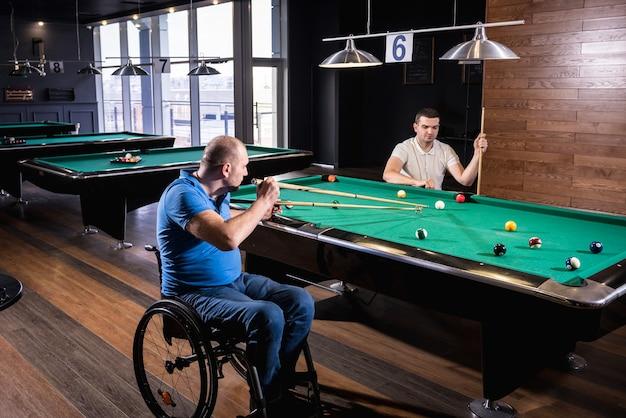 Dorośli niepełnosprawni mężczyźni na wózku inwalidzkim grają w klubie w bilard