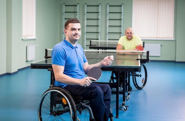 Dorośli niepełnosprawni mężczyźni na wózku inwalidzkim, grający w tenisa stołowego