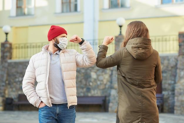 Dorosli przyjaciele w maskach na twarz uderzają łokciem zamiast witać się uściskiem dłoni