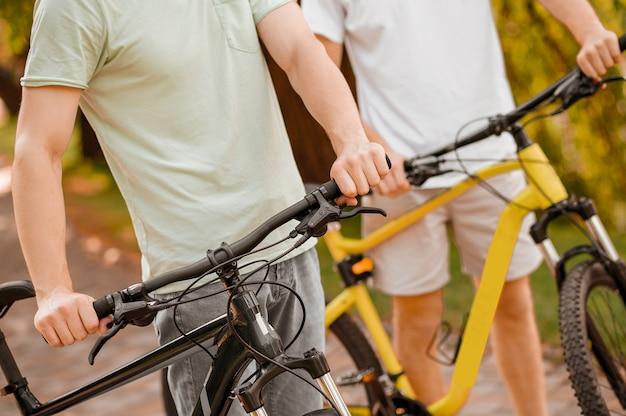 Dorośli wysportowani mężczyźni na rowerze w parku