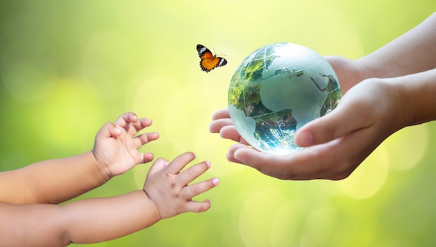 Dorośli wysyłają świat do niemowląt. concept day earth uratuj świat, ocal środowisko. świat jest na trawie