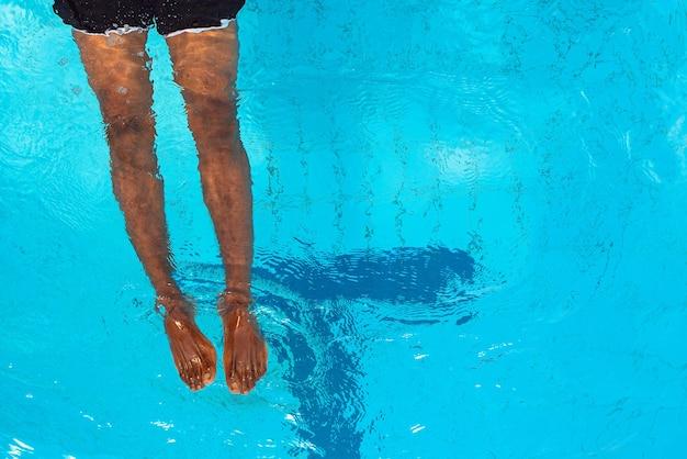 Dorosły afroamerykanin ma nogi pod wodą w basenie