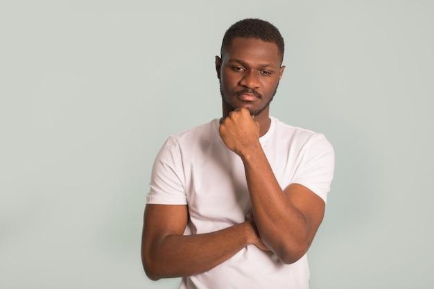 Dorosły afrykański mężczyzna w białej koszulce ze smutną twarzą na niebieskim tle