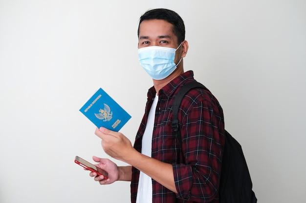 Dorosły azjata ubrany w ochronną maskę medyczną, trzymający telefon komórkowy i paszport kraju indonezji