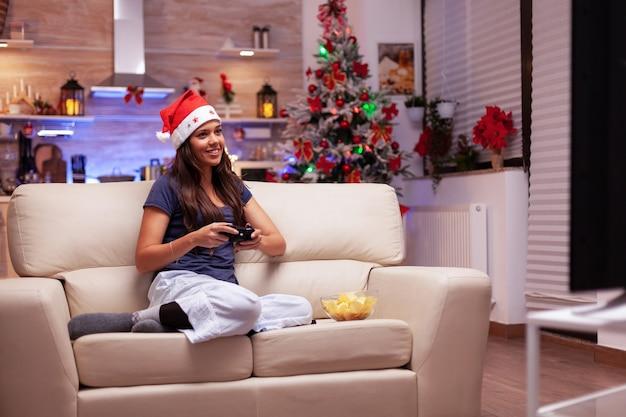 Dorosły bawiący się w świątecznej udekorowanej kuchni, grający w gry wideo online w celu rywalizacji w grach