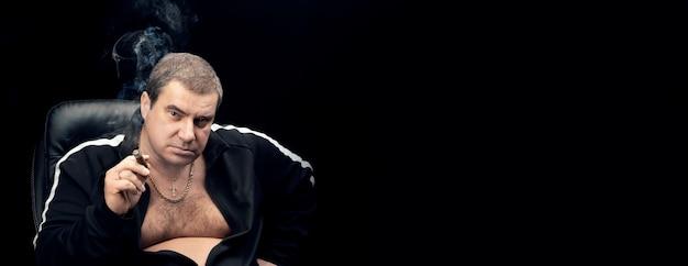 Dorosły biały mężczyzna w dresie siedzi na krześle i pali cygaro, patrząc w kamerę. organ karny, demontaż, kopia przestrzeń