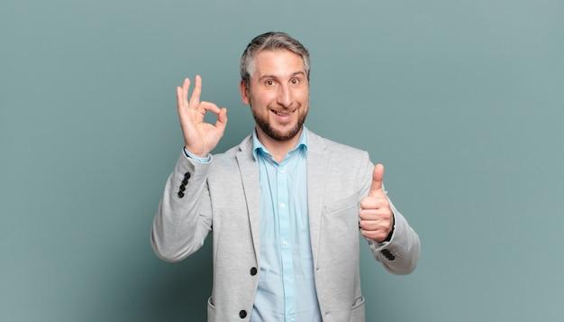 Dorosły biznesmen czuje się szczęśliwy, zdumiony, zadowolony i zaskoczony, pokazując gesty w porządku i kciuki w górę, uśmiechając się up