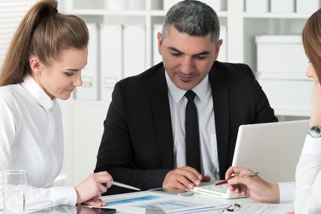 Dorosły biznesmen konsultacji z młodą koleżanką podczas spotkania biznesowego. partnerzy omawiający dokumenty i pomysły