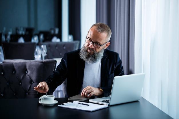 Dorosły biznesmen pracuje nad nowym projektem i patrzy na wykresy wzrostu akcji. siedzi przy stole przy dużym oknie. patrzy na ekran laptopa i pije kawę.