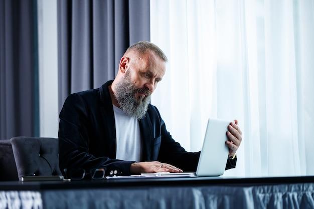 Dorosły biznesmen pracuje nad nowym projektem i patrzy na wykresy wzrostu akcji. siedzi przy stole przy dużym oknie. patrzy na ekran laptopa i się uśmiecha
