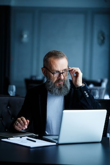 Dorosły biznesmen pracuje nad nowym projektem i patrzy na wykresy wzrostu akcji. siedzi przy stole przy dużym oknie. patrzy na ekran laptopa
