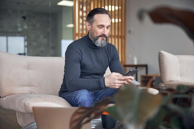 Dorosły biznesmen siedzi i chłodzi w przytulnej przestrzeni biurowej
