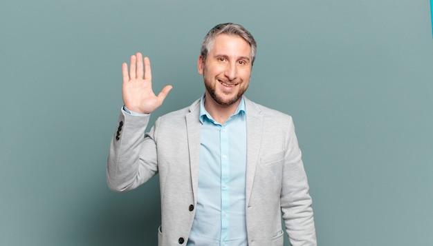 Dorosły biznesmen uśmiecha się radośnie i radośnie, machając ręką, witając cię i witając lub żegnając się