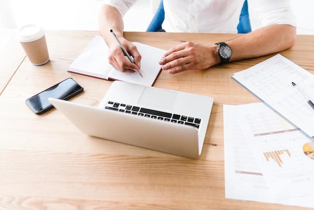 Dorosły biznesmen w białej koszuli siedzi przy stole i zapisywanie informacji ołówkiem w notesie, podczas pracy w biurze