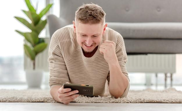 Dorosły blondyn leży na dywanie i gra w gry na smartfonie