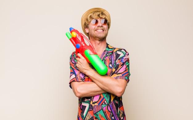 Dorosły blondyn na wakacjach trzyma pistolet na wodę