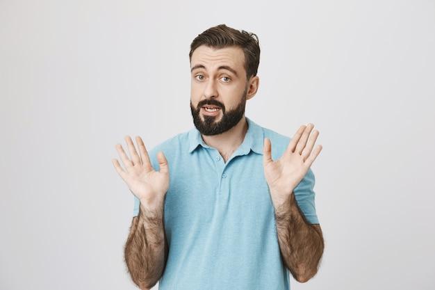 Dorosły brodaty mężczyzna mówi i pokazuje puste ręce