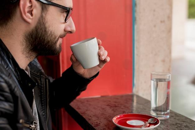 Dorosły brodaty mężczyzna pije napój przy kawiarnią