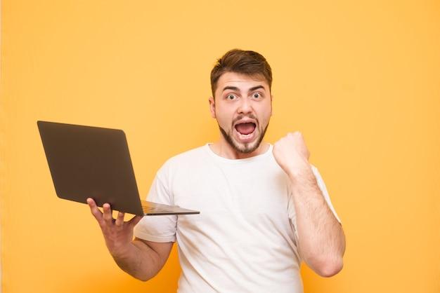 Dorosły brodaty nastolatek ubrany w białą koszulkę na żółtym tle trzyma laptopa w ręku, raduje się ze zwycięstwa