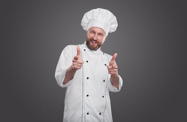 Dorosły brodaty profesjonalny kucharz w białym mundurze szefa kuchni, uśmiechając się i wskazując na aparat z kciukami do góry na szarym tle