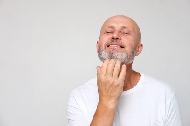 Dorosły brodaty śmiały, siwy mężczyzna drapie się po brodzie, na szarym tle