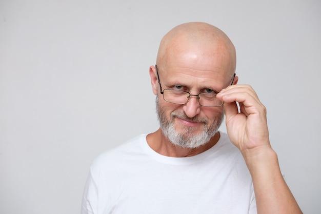 Dorosły, brodaty, śmiały, siwy mężczyzna w okularach, patrzący na ziarno soli (sceptycznie) lub pytająco na szarym tle