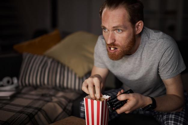 Dorosły człowiek ogląda moview nocą