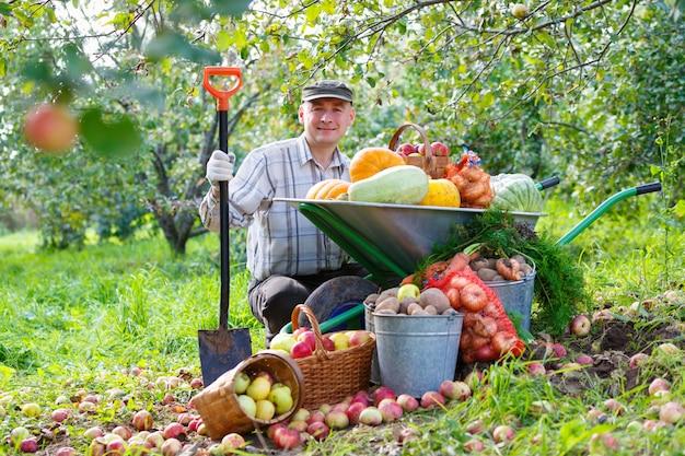 Dorosły człowiek w ogrodzie z bogatymi zbiorami