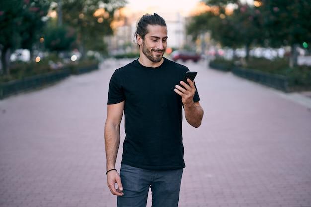Dorosły długowłosy mężczyzna idzie po ulicy mając telefon służbowy