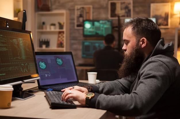 Dorosły haker wpisujący wirusa na komputerze w celu złamania zabezpieczeń zapory. młody haker w tle.