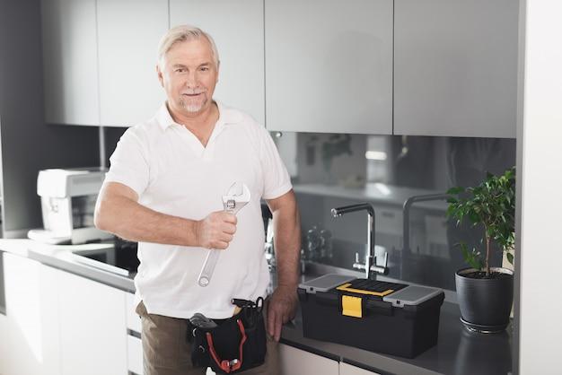 Dorosły hydraulik trzyma klucz kuchnia pozowanie.
