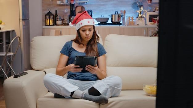 Dorosły korzystający z cyfrowego tabletu i oglądający film w telewizji