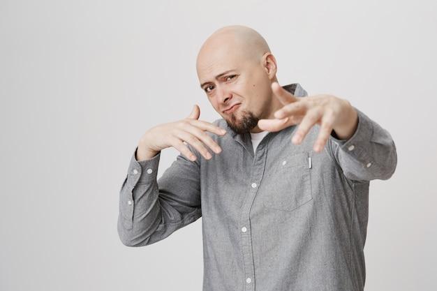 Dorosły łysy brodaty mężczyzna śpiewa rap i tańczy hip hop