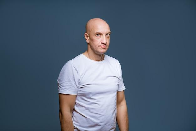 Dorosły łysy mężczyzna w białej koszulce pozuje emocjonalnie na niebieskim tle portret zrobiony w zbliżeniu w...