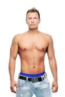 Dorosły mężczyzna bez koszula pozuje w studiu