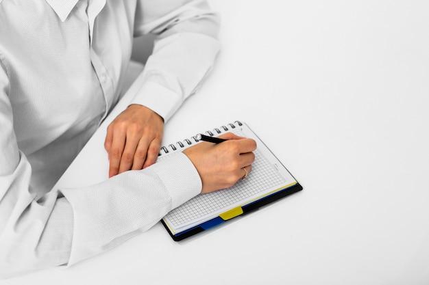 Dorosły mężczyzna bierze notatki przy biurem