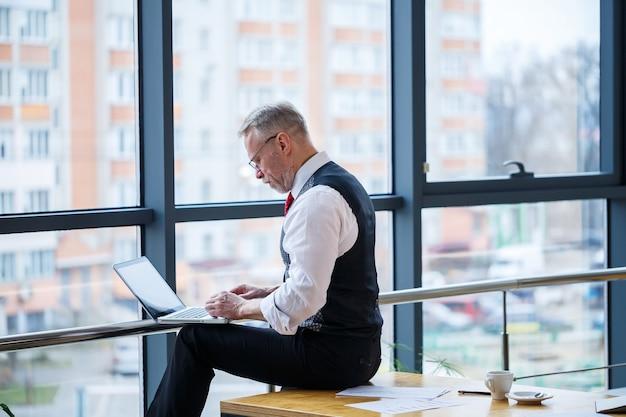 Dorosły mężczyzna biznesmen, nauczyciel, mentor pracujący nad nowym projektem. siedzi przy dużym oknie na stole. patrzy na ekran laptopa.