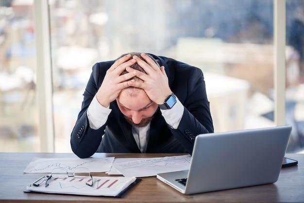 Dorosły mężczyzna biznesmen, nauczyciel, mentor pracuje nad nowym projektem w biurze i jest zdenerwowany. siedzi przy stole przy dużym oknie. pracuje na laptopie, problemy biznesowe