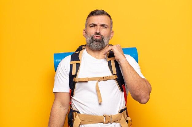 Dorosły mężczyzna czuje się zestresowany, niespokojny, zmęczony i sfrustrowany, ciągnie za szyję koszuli, wygląda na sfrustrowanego problemem