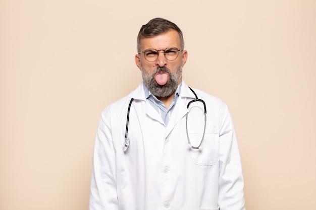 Dorosły mężczyzna czuje się zniesmaczony i zirytowany, wysuwa język, nie lubi czegoś paskudnego i obrzydliwego