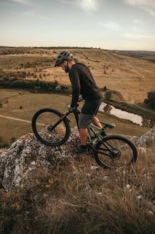 Dorosły mężczyzna jedzie na rowerze na pagórkowatym terenie o zachodzie słońca