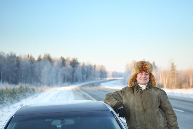 Dorosły mężczyzna kierowca samochodu na tle zimowego nieba