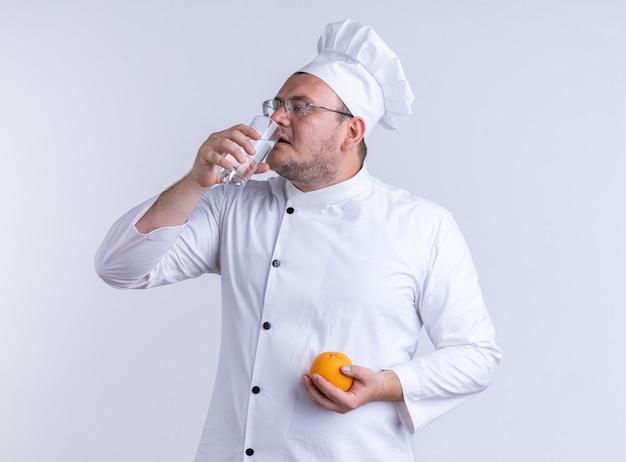 Dorosły mężczyzna kucharz w mundurze szefa kuchni i okularach trzymających pomarańczę, patrząc na bok, pijący szklankę wody na białej ścianie